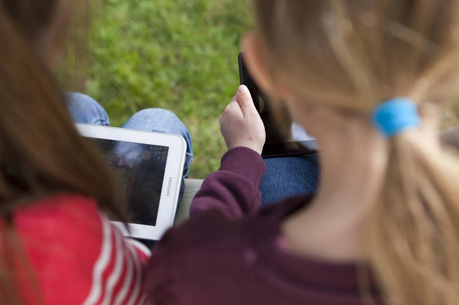 Zwei kleine Mädchen schauen auf ihre Tablet-Computer