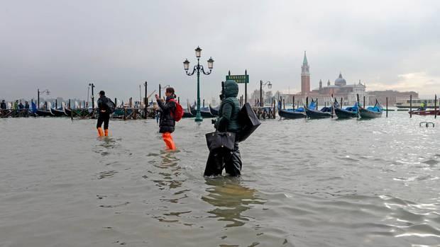 Menschen waten über einen überfluteten Platz in Venedig