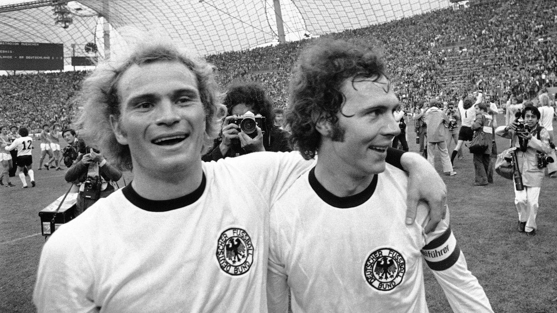 Uli Hoeneß (l.) und Franz Beckenbauer nach dem Sieg im WM-Finale1974 gegen die Niederlande im Münchner Olympiastadion.Zwei Jahre zuvor war er schon im zarten Alter von 20 JahreEuropameister geworden.