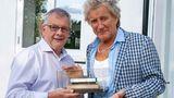 """Steve Flint, Chefredakteur der britischen Fachzeitschrift """"Railway Modeller"""" überreichtRod Stewart ein Modelleisenbahn-Waggon"""