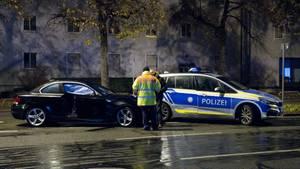 München: Polizisten stehen nach dem Unfall auf der Fürstenrieder Straße neben dem beschädigten Auto