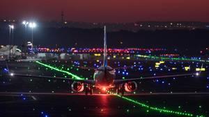 EinPassagierflugzeug rollt im letzten Licht der untergehenden Sonne über die Rollbahn des Flughafens Frankfurt