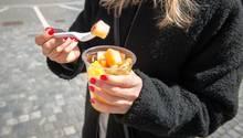 Eine junge Frau isst Obstsalat aus dem Supermarkt