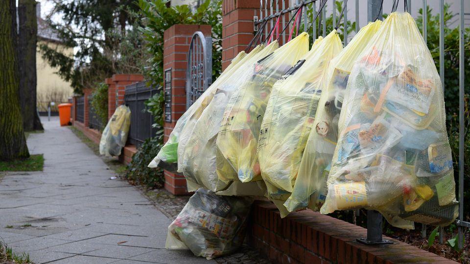 In Berlin hängen gefüllte gelbe Müllsäcke an einem Gartenzaun zur Abholung bereit