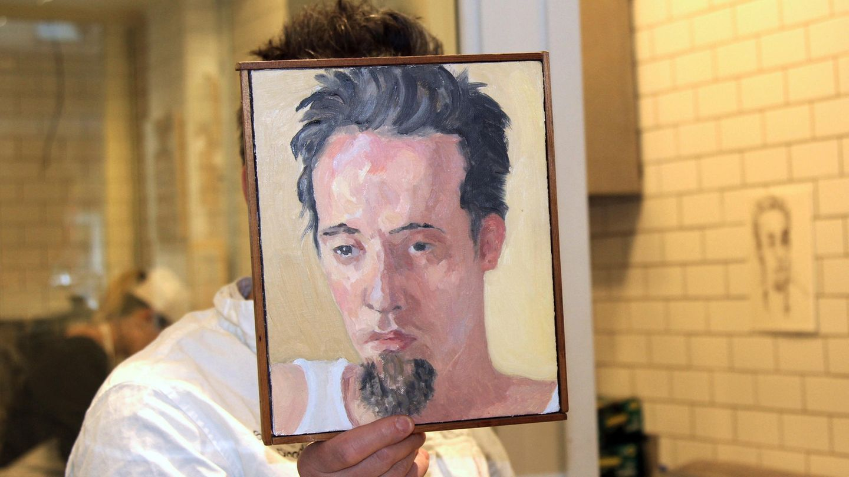 """Sebastian Brecht hält sich in seinem Laden, wo er jeden Monat einen anderen Künstler ausstellt, ein Portrait vor sein Gesicht, das die Künstlerin Alix Bailey von ihm gemalt hat - er lässt sich nie fotografieren. Der Enkel des Dichters und Dramatikers Brecht hat im East Village das Schokoladen-Geschäft """"Obessive Chocolate Disorder""""eröffnet."""
