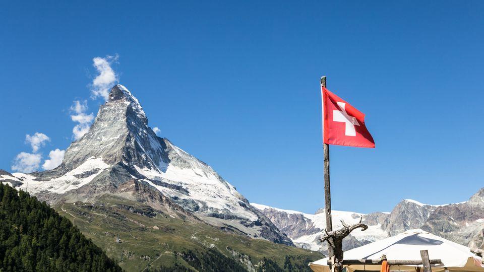 Das Matterhorn und eine Schweizer Flagge davor