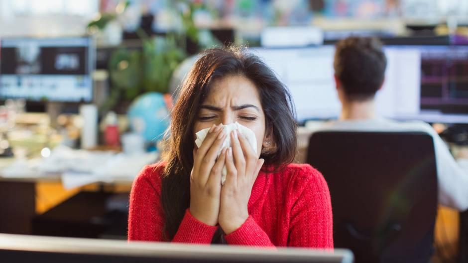 Erkältung vorbeugen: Eine Frau niest in ein Taschentuch