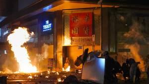 Demonstranten schützen sich auf dem Campus der Universität in Hongkong mit Regenschirmen vor Tränengasgeschossen