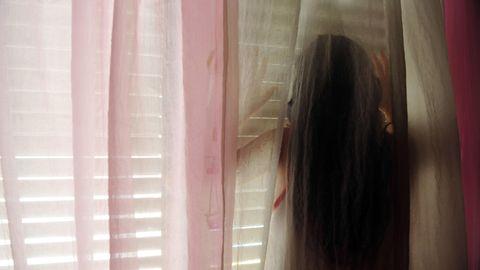 Die Silhouette einer Frau ist hinter einem Vorhang zu sehen