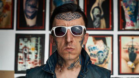 Ein Mann mit Tätowierungen auf der Stirn, den Wangen, am Kinn und am Hals
