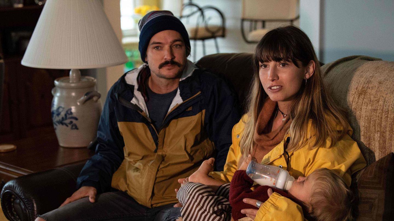 Ein Mann mit Schnauzbart sitzt links auf einem Sofa, rechts gibt eine Frau mit dunkelblonden Haaren einem Jungen die Flasche
