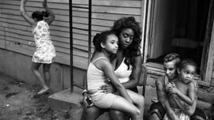 Eine Mutter sitzt mit ihren Kinder vor einem Holzhaus