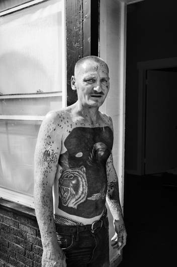 Ein tätowierter Mann mit einem nächtlichen Tattoomotiv auf dem Bauch