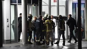 Feuerwehrleute, Polizisten und medizinisches Personal stehen nach dem Vorfall vor der Klinik