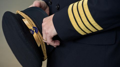 Ein Pilot der Lufthansa hält seine seine Pilotenmütze in der Hand.