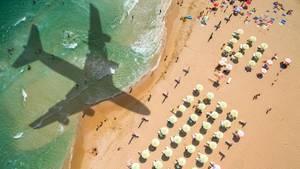 Der Schatten eines Flugzeugs über Meer und Strand