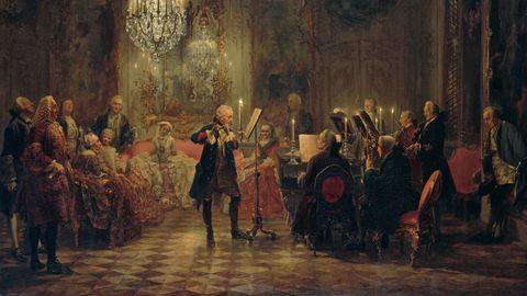 Ein Gemälde auf dem Friedrich der Große abgebildet ist. Er spielt Querflöte, begleitet vom Kammerorchester