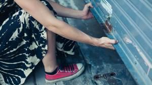 Frauenhände öffnen ein Garagentor