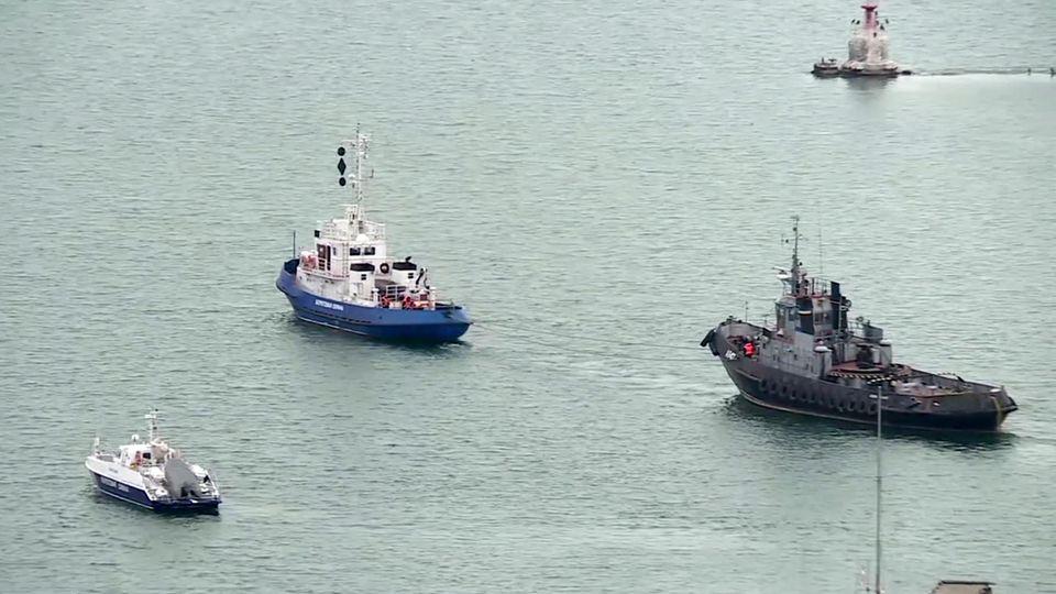 Ein beschlagnahmtes ukrainisches Schiff (r) wird aus dem Hafen von Kertsch geschleppt