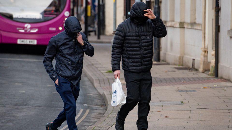 Zwei Männer ziehen ihre Kapuzen ins Gesicht, um nicht erkannt zu werden
