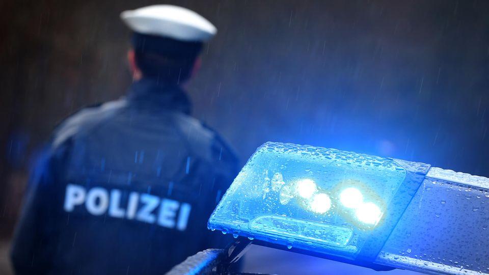 News von heute: Ein Polizist steht neben einem Einsatzwagen mi Blaulicht