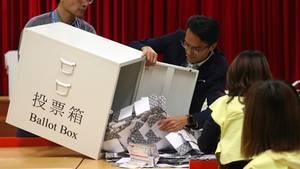 Wahlhelfer leeren eine Wahlurne in einem Wahllokal