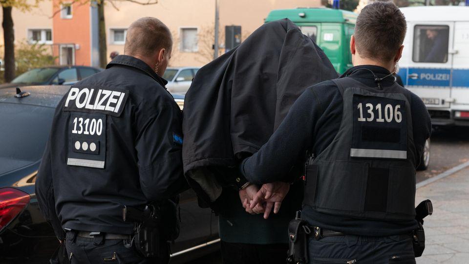 Polizeibeamte führeneinen festgenommenen Mannab