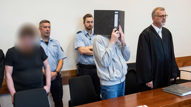 Die Angeklagten Mario S. (l-r) und Andreas V. stehen im Gerichtssaal des Landgerichts nebeneinander
