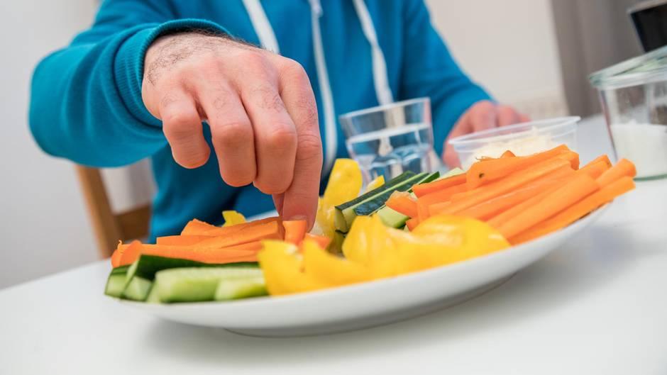 Ein Mann isst Gemüse