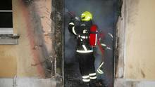 Ein Feuerwehrmann löscht im Inneren des brennenden Amtshauses.