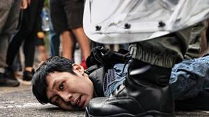 Chinesische Polizisten nehmen einen der Demonstranten fest