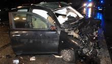Ein total demoliertes Auto in der Dunkelheit