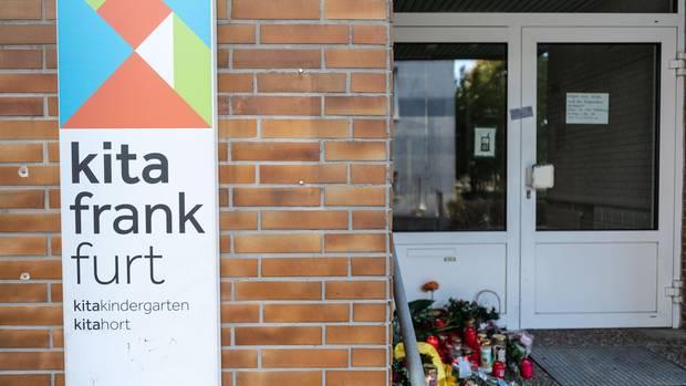 Blumen und Kerzen (r) sind am Eingang zu einer Kindertagesstätte im Stadtteil Seckbach abgelegt.