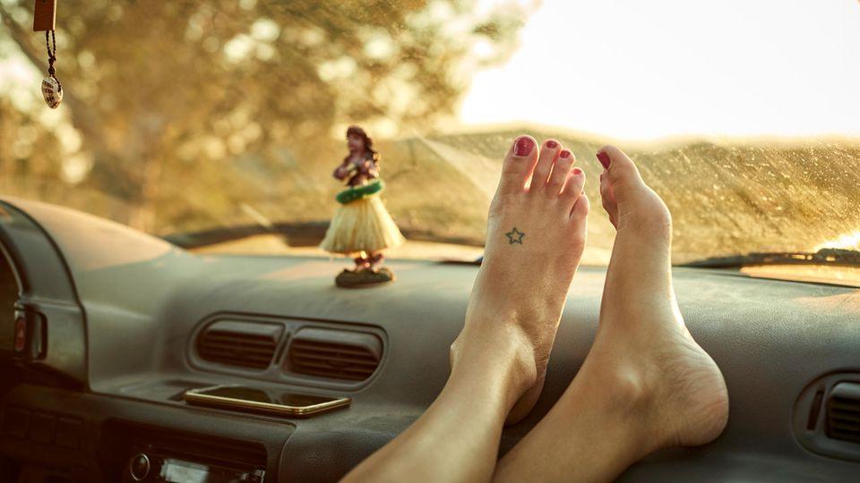 Nahaufnahme von Füßen auf dem Armaturenbrett eines Autos. Ein kleiner Stern ist auf dem linken Fuß tätowiert.