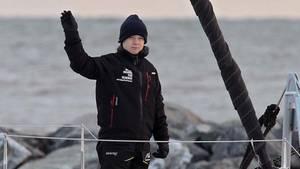 Ein Mädchen steht in schwarzer Regenkleidung am Bug einer Segeljacht und winkt