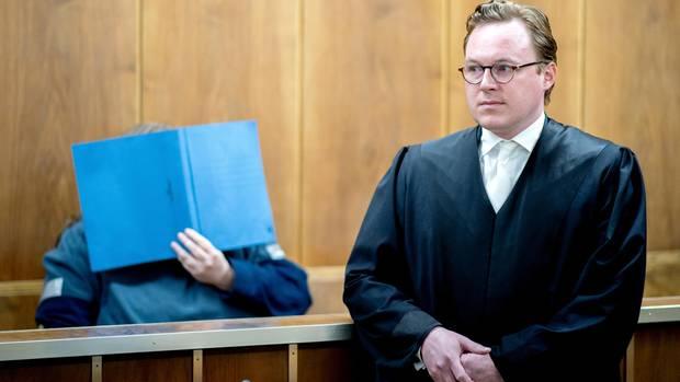 Der angeklagte Sohn sitzt mit einem Aktendeckel vor dem Gesicht hinter seinem Verteidiger Pascal Ackermann im Gerichtssaal. Im Prozess gegen einen Waffensammler, der in rechtsextremen Internet-Foren unterwegs war, wurde am Mittwoch das Urteil gesprochen.
