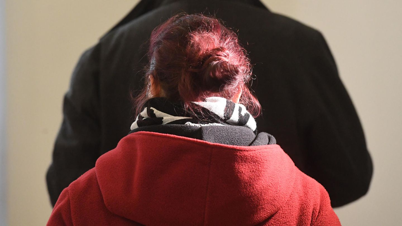 Eine Frau mit rot gefärbten, zum Dutt gesteckten Haaren wendet der Kamera den Rücken zu