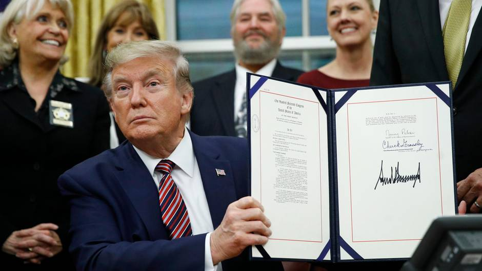 US-Präsident Donald Trump hält eine Mappe mit einem Gesetz hoch, das er gerade im Oval Office unterschrieben hat