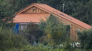 Ein Gebäude mit rotem Ziegeldach und hölzerner Verschalung ist hinter Büschen zu sehen