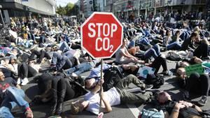 """Auf einer Kreuzung in Düsseldorf liegen lauter Demonstranten. Einer hält ein Stoppschild mit mit """"Stop CO2"""" hoch"""