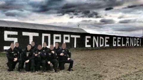"""Neun Polizisten in Uniform knien auf einem Knie vor einem """"Stoppt Ende Gelände!""""-Graffito"""