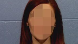 Eine Frau mit rotbraunen, halblangen Haaren sitzt in violettem Oberteil vor einer grauen Mauer und schaut direkt in die Kamera