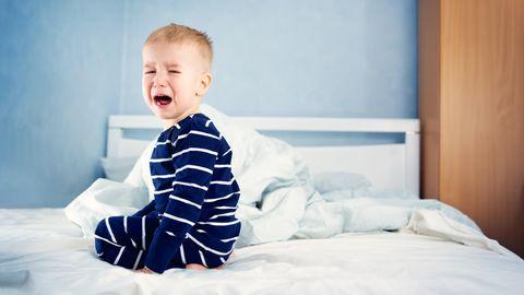 Ein Junge hockt weinend auf einem Bett
