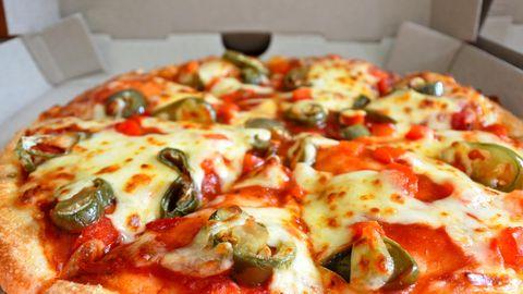 In einem weißen Pizzakarton leiget eine dick belegte Pizza mit Salami, Jalapenos und Käse