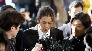 Ein Asiate mit zurückgebundenen langen Haaren spricht in Mikrofone, die Reporter dem jungen Mann hinhalten