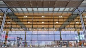 """An einer gläsernen Terminal-Fassade leuchtet der Schriftzug """"Flughafen Berlin-Brandenburg Willy Brandt"""""""