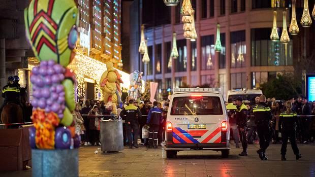 Niederlande, Den Haag: Polizisten stehen in einer Einkaufsstraße.
