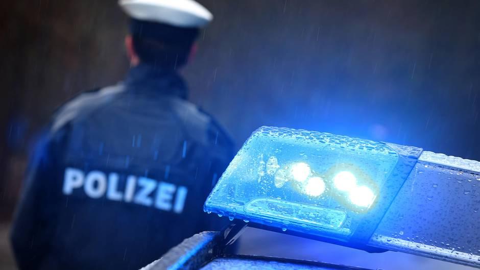 Ein Polizist steht im Regen vor einem Streifenwagen dessen Blaulicht aktiviert ist