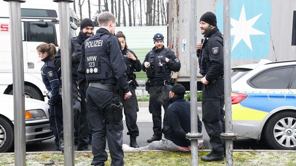 Polizisten umringen einen Festgenommenen, der auf dem Boden sitzt