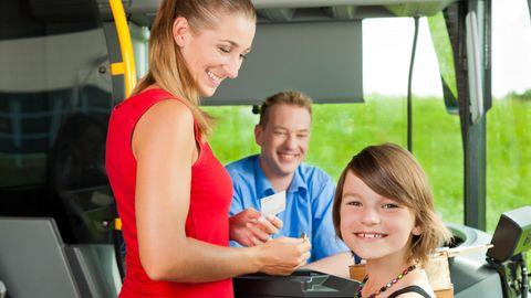 Eine Frau und ein Kind kaufen im Bus ein Nahverkehrsticket